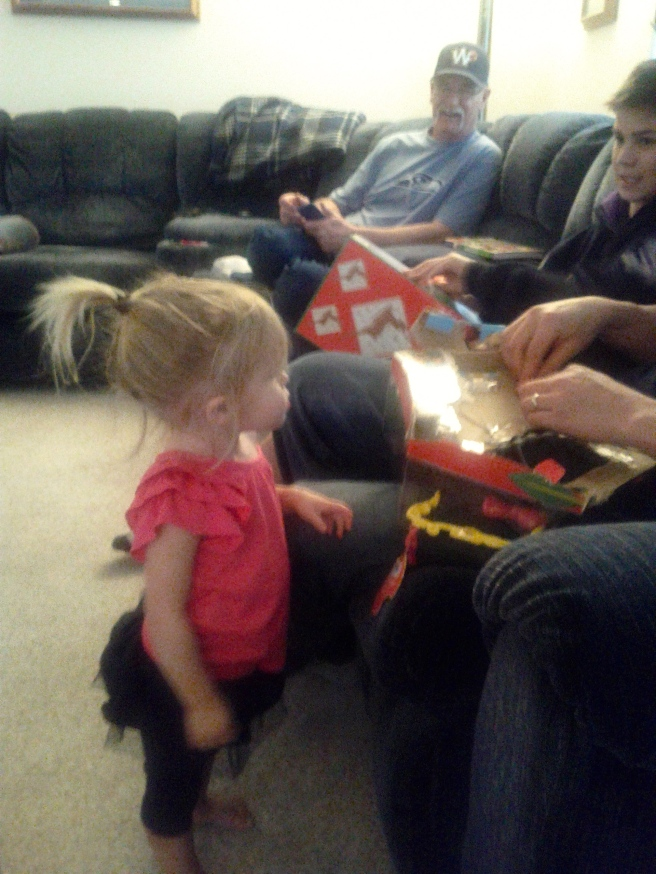Kaili waiting patiently for Uncle to open her doll.