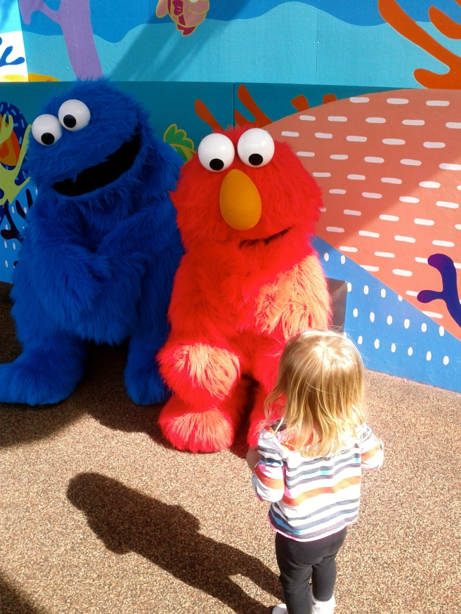 Kaili saw Elmo and ran to him but slowly backed away as he went for a high five.